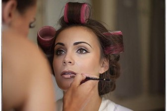 bride has her makeup applied before the wedding