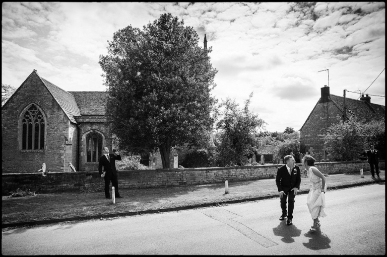A storytelling wedding image showing the bride and groom laughing at each other outside the church