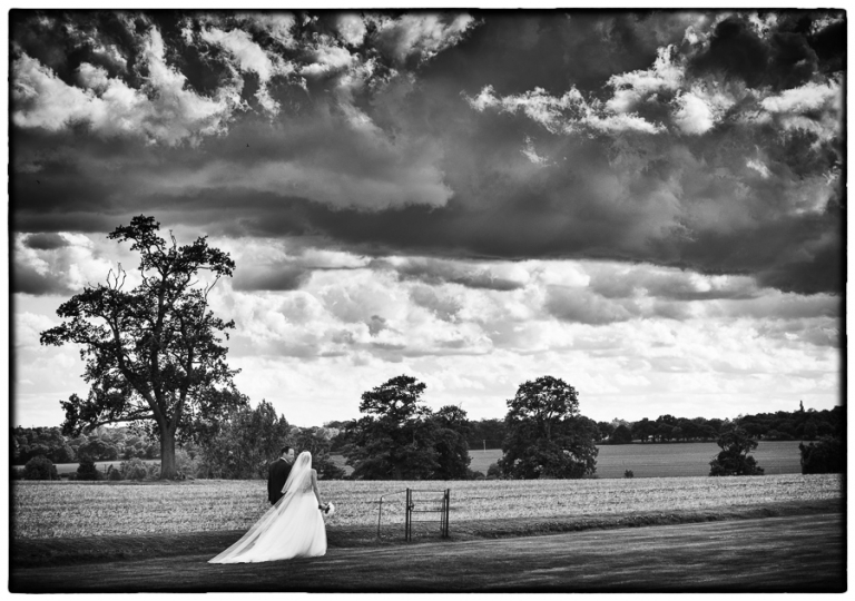 Blake Hall wedding photography with the bride and groom walking through the grounds.