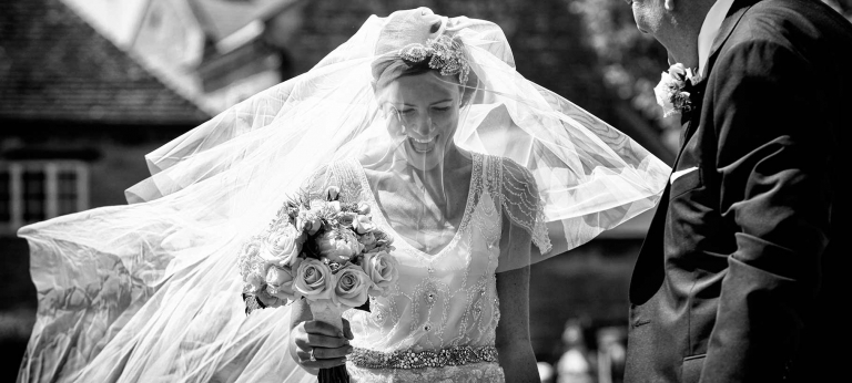 reportage wedding photography showing the bride smiling as her veil is lifted by the wind
