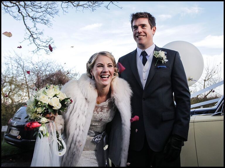 winter wedding photography with the bride and groom leaving church